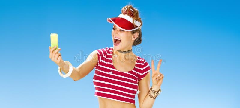Женщина на пляже принимая selfie с мобильным телефоном и показывая победу стоковые изображения rf