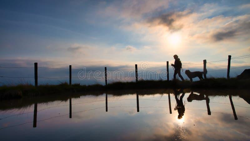 Женщина на походе горы с ее любимой собакой на заходе солнца стоковое изображение rf
