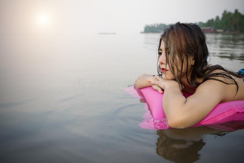 Женщина на раздувной кровати бассейна наслаждаясь загорать солнца стоковые фотографии rf