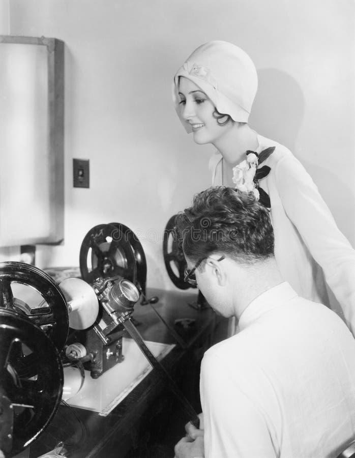 Женщина на редактируя машине с фильмом редактора рассматривая (все показанные люди более длинные живущие и никакое имущество не с стоковые фото