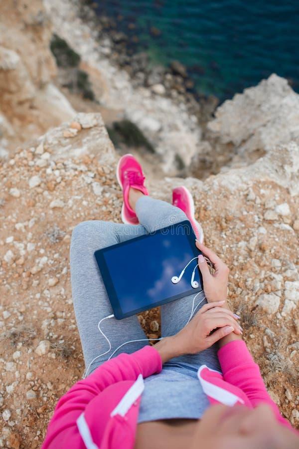 Женщина на скалистом пляже с таблеткой весной стоковое фото rf