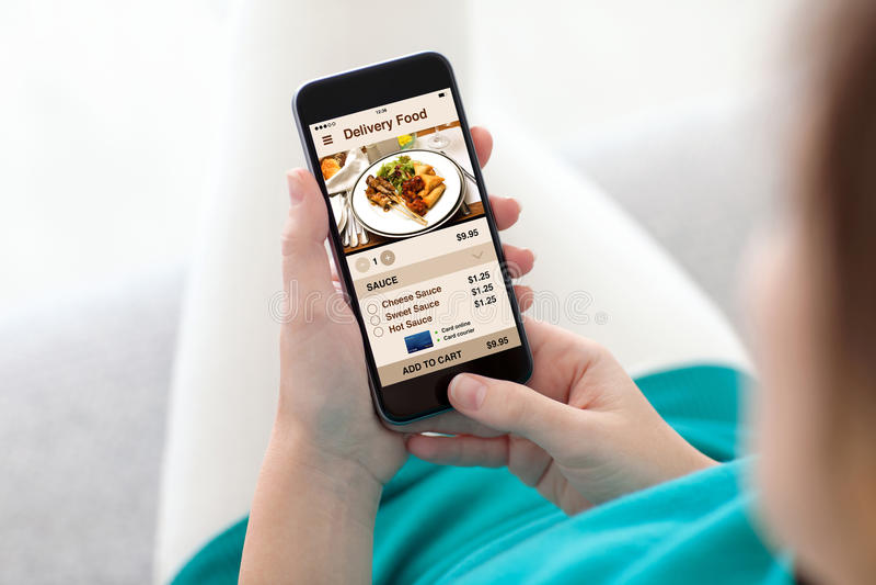 Женщина на софе держа телефон с экраном еды поставки app стоковые изображения rf