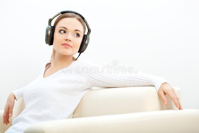 Женщина на софе слушая к нот стоковые изображения