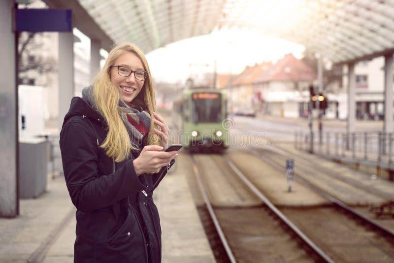 Женщина на станции с причаливая поездом стоковая фотография rf
