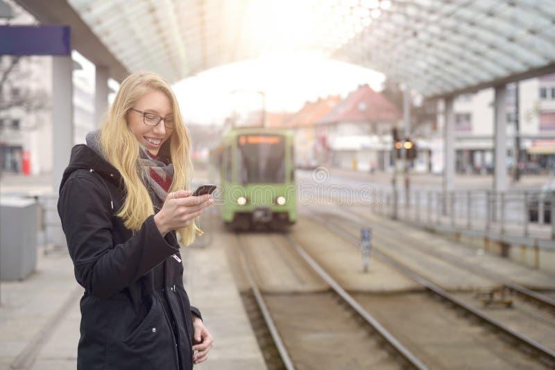 Женщина на станции с причаливая поездом стоковое изображение