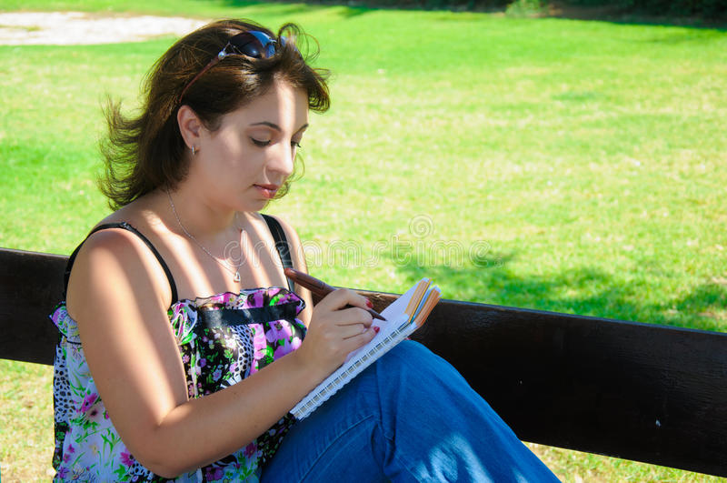 Женщина на стенде пишет в ее блокнот стоковая фотография rf