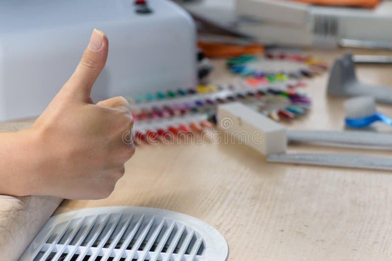 Женщина на студии ногтя показывая большой палец руки вверх стоковая фотография rf