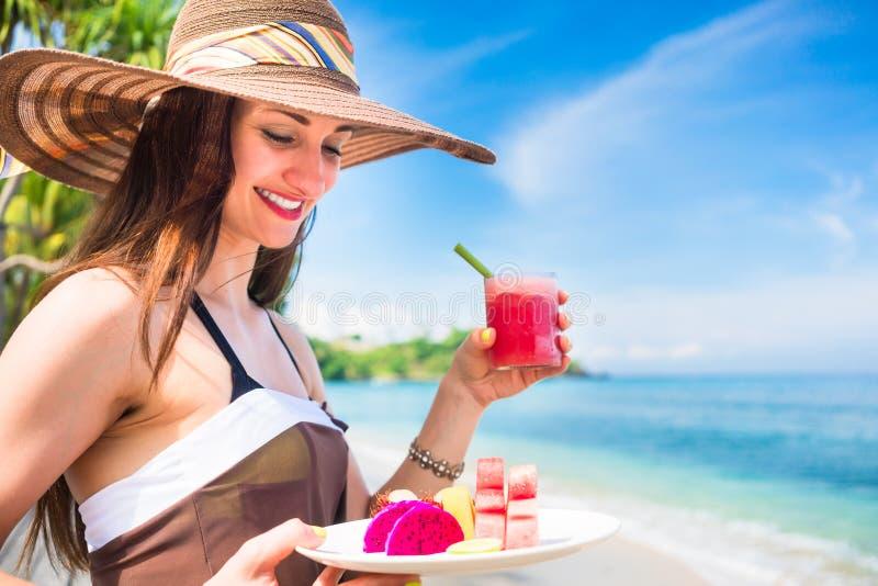 Женщина на тропическом пляже есть плодоовощ для завтрака стоковые изображения
