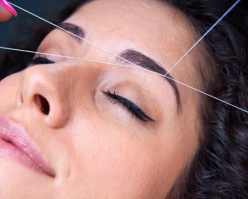 Женщина на удалении волос на лице продевая нитку процедуру стоковое фото rf