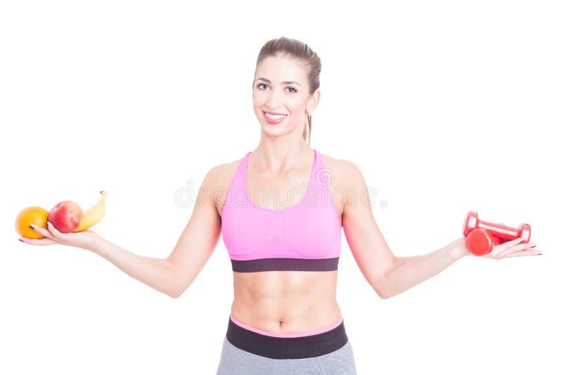 Женщина на удерживании спортзала приносить и весы как баланс стоковая фотография
