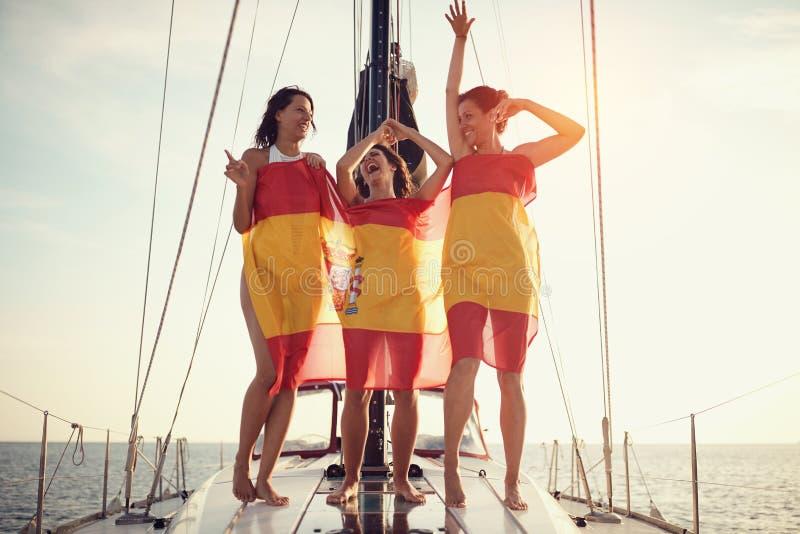 Женщина на яхте в испанском флаге имея партию стоковое фото