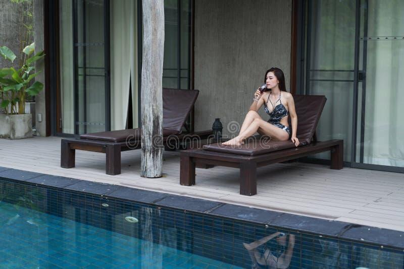 Женщина на deckchair и держать стеклянный в бассейне стоковое изображение
