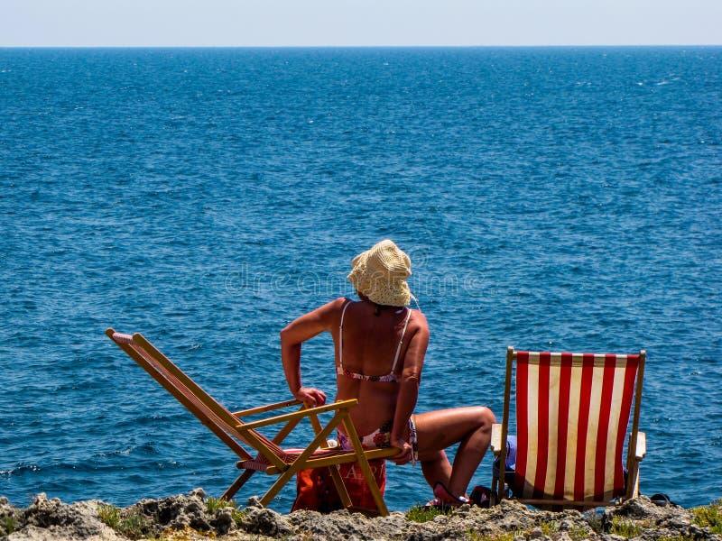 Женщина на deckchair морем стоковое изображение