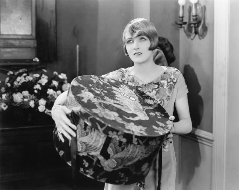 Женщина нося большую коробку шляпы (все показанные люди более длинные живущие и никакое имущество не существует Гарантии поставщи стоковое изображение
