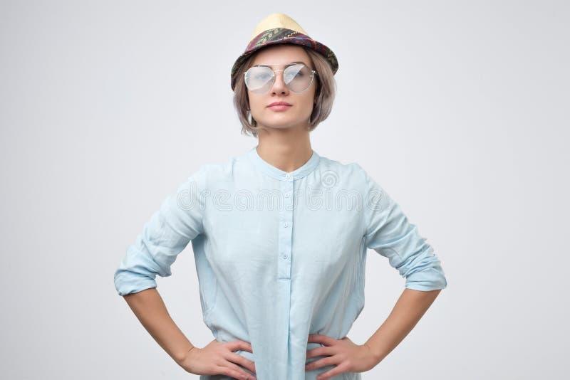 Женщина нося круглую шляпу лета, стекла лета и голубую рубашку стоковое фото rf