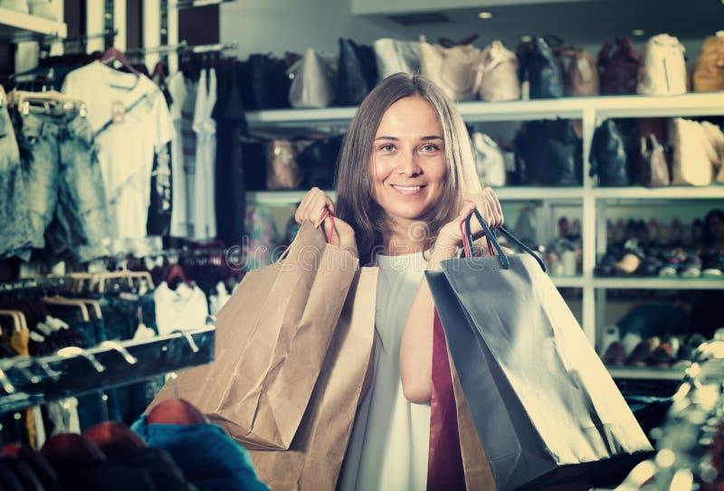 Женщина нося много бумажных сумок стоковые изображения