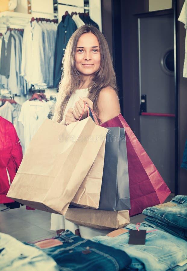 Женщина нося много бумажных сумок стоковое фото