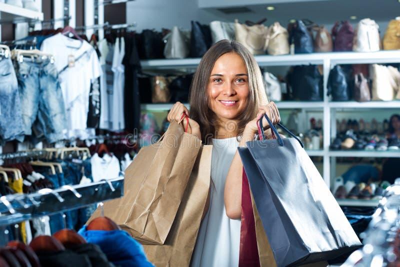 Женщина нося много бумажных сумок стоковое фото rf