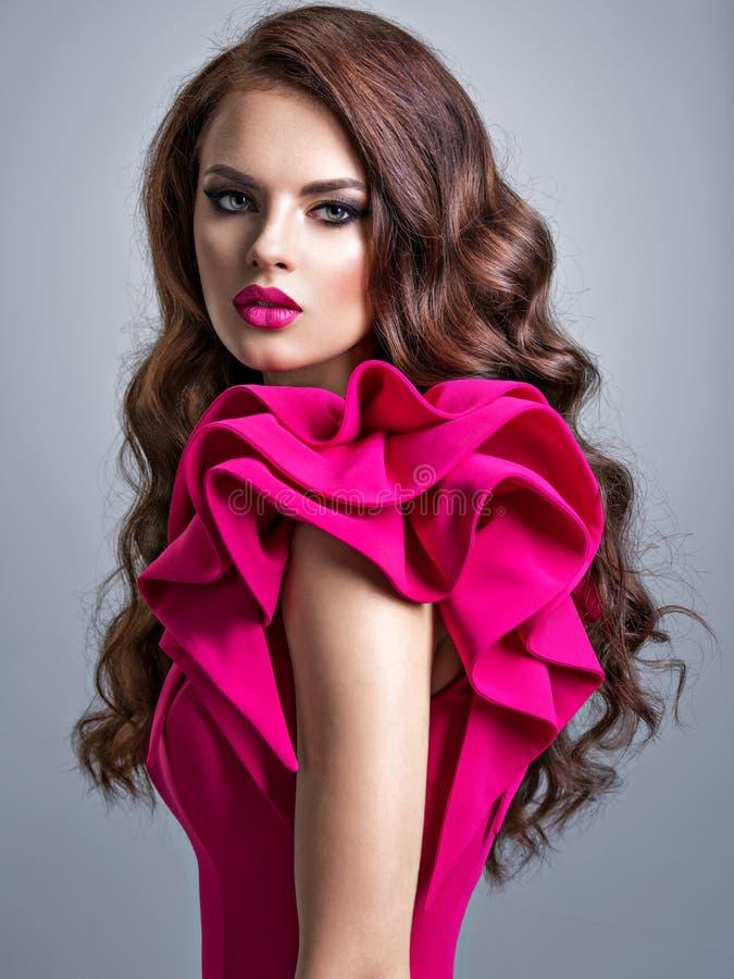Женщина нося модное красное платье с творческим стилем причесок стоковая фотография rf