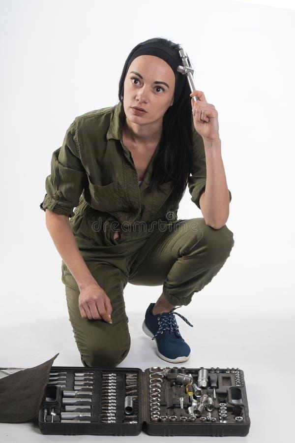 Женщина нося пояс инструмента DIY вполне разнообразие полезных инструментов на белой предпосылке Женщина конструкции стоковое изображение rf