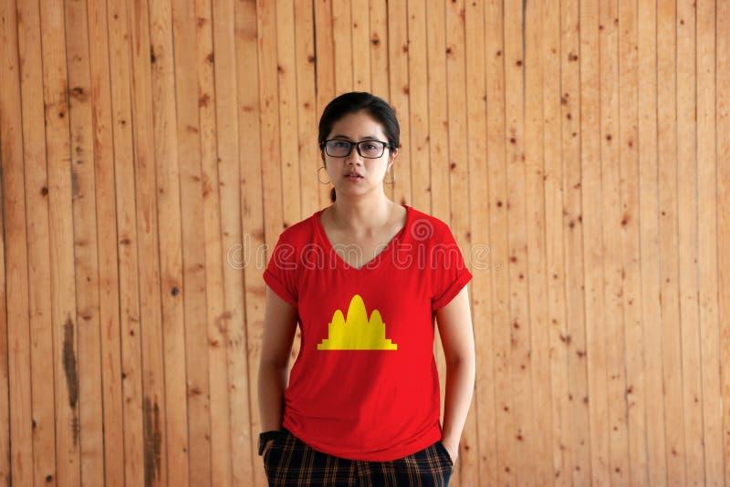 Женщина нося рубашку цвета флага Democratic Kampuchea и стоя с 2 руками в карманах тяжелого дыхания на деревянной предпосылке сте стоковые изображения