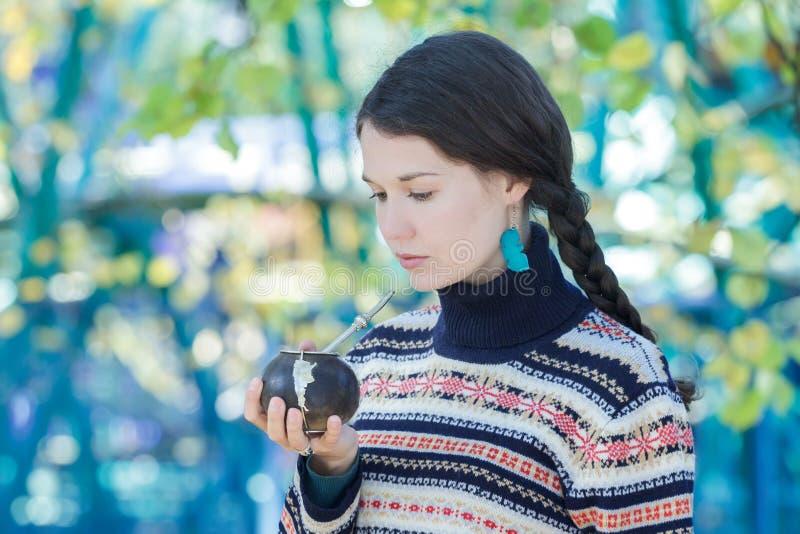 Женщина нося связанные снежинки делает по образцу серьги свитера и бирюзы выпивая горячую ответную часть yerba стоковая фотография