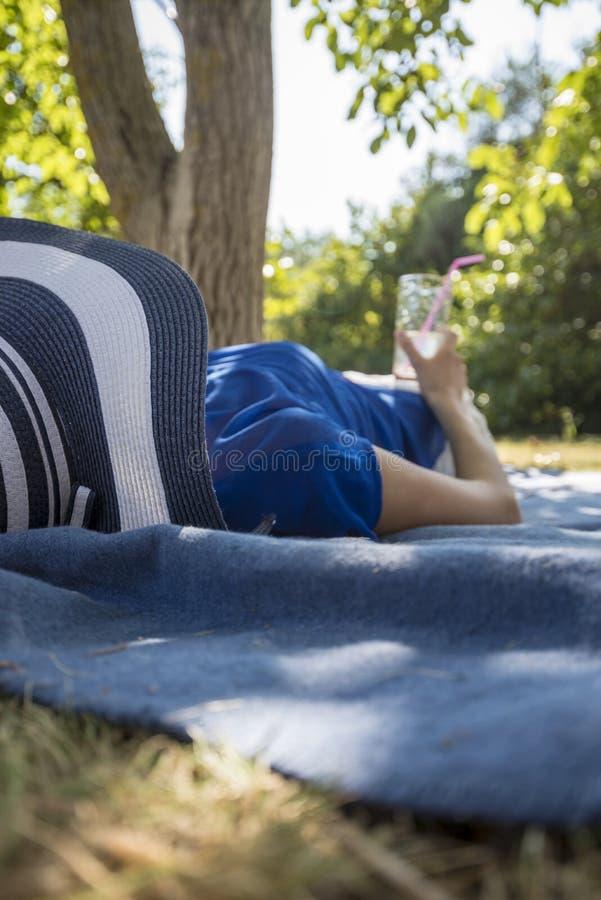 Женщина нося соломенную шляпу ослабляя путем лежать в природе лета стоковое фото rf