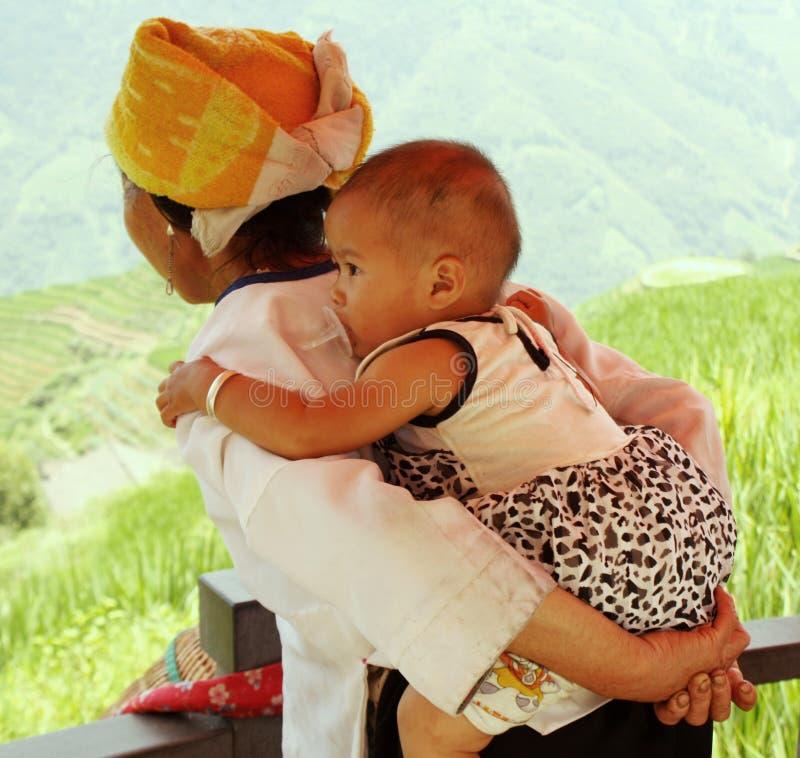 женщина нося фарфора ребенка стоковые фотографии rf