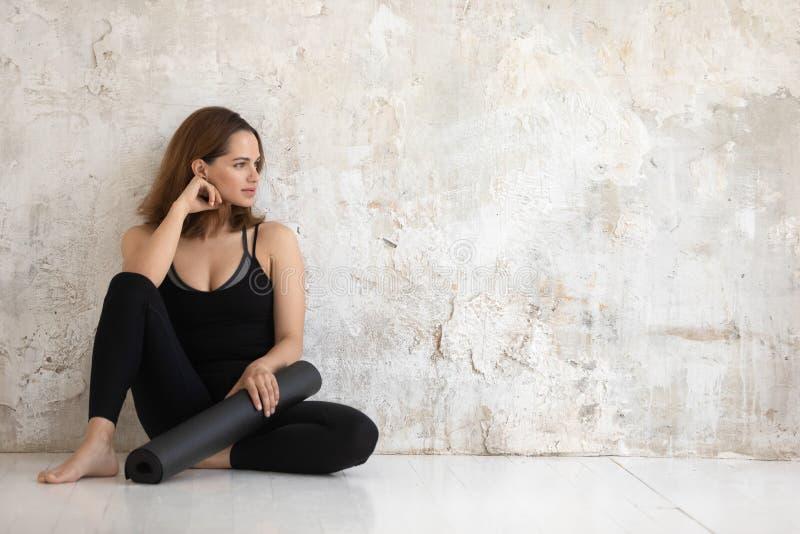 Женщина нося черную циновку удерживания sportswear полагается против стены стоковое фото