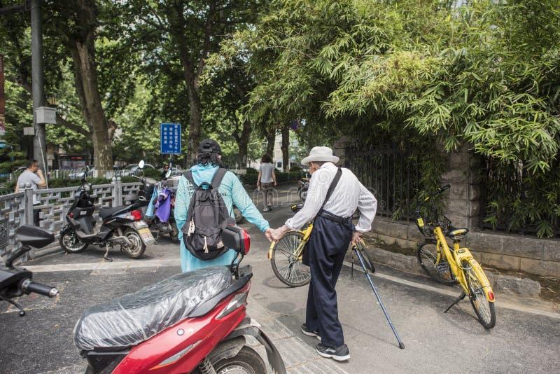 Женщина нося шляпу и идя ручку нося белое пальто и humpbacked пожилую женщину идя в улицу стоковая фотография rf