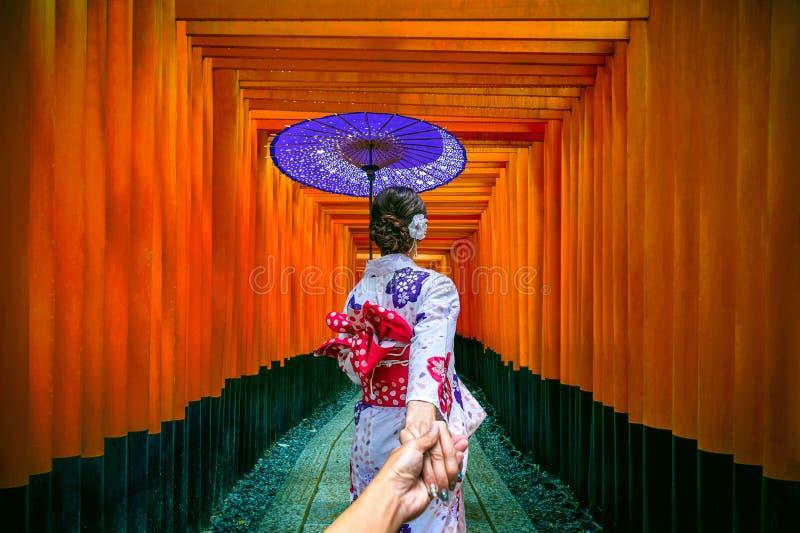 Женщина нося японское традиционное кимоно держа руку ` s человека и водя его к дорожке стробов на святыне taisha inari fushimi стоковое изображение