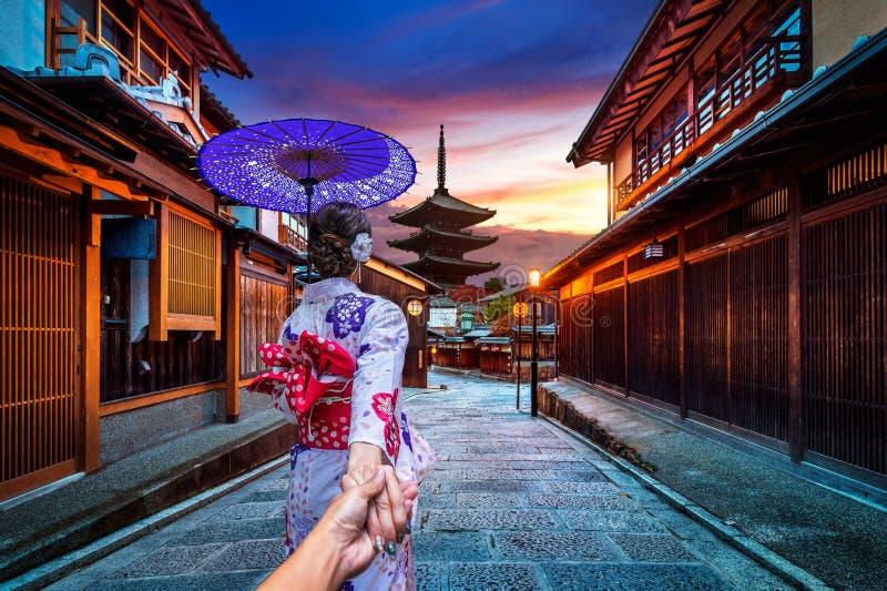 Женщина нося японское традиционное кимоно держа руку ` s человека и водя его к пагоде Yasaka и улицу Sannen Zaka в Киото стоковое изображение