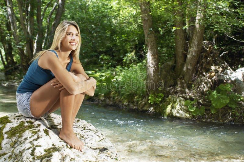 Женщина обнимая колени пока смотрящ прочь рекой леса стоковые изображения rf