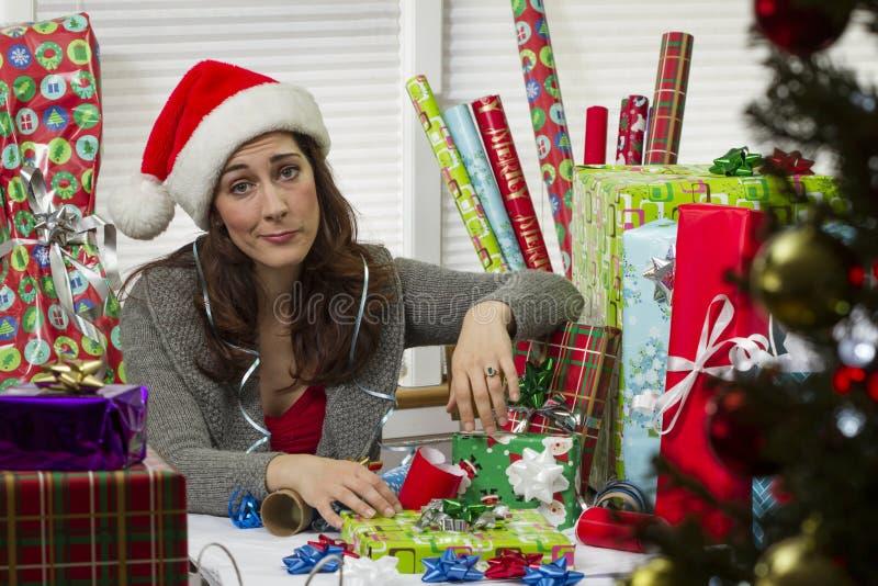 Женщина оборачивая подарки на рождество, смотря вымотанный стоковое изображение rf