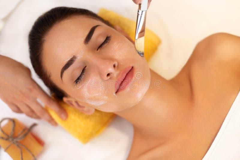 женщина обработки лицевого щитка гермошлема огурца белая Женщина в салоне красоты получает морскую маску стоковое фото
