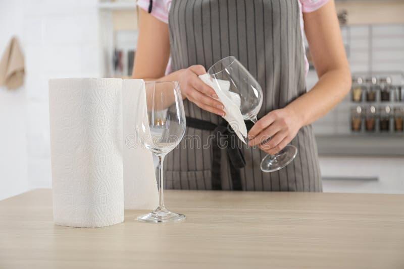 Женщина обтирая бокал с бумажным полотенцем в кухне, стоковые фото