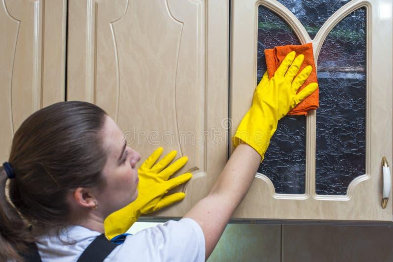 Женщина обтирая кухонный шкаф кухни с ветошью стоковое фото rf