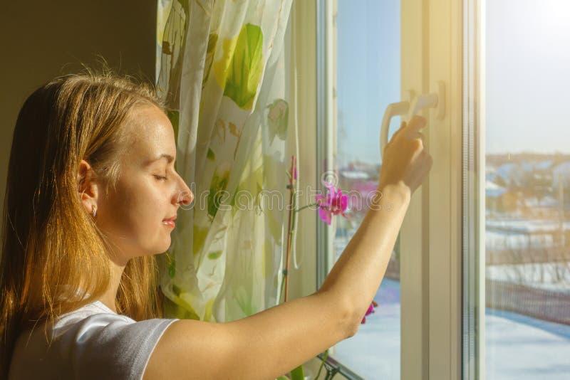 Женщина окно отверстия и дышая свежий морозный воздух в снежных горах стоковая фотография