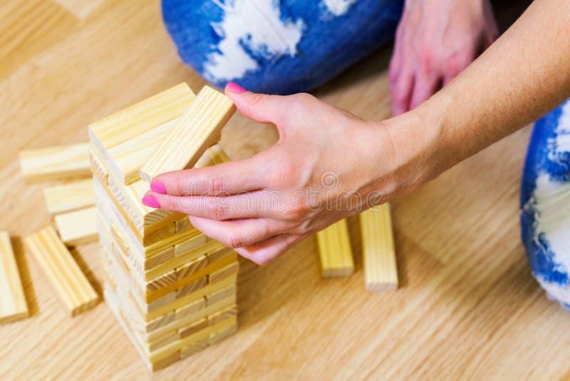 Женщина около деревянной игры башни стоковые фотографии rf