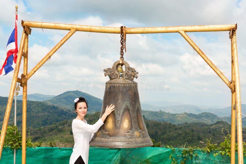Женщина около тайского гонга в Пхукете Колокол традиции азиатский в виске буддизма в Таиланде Известное большое желание колокола  стоковые изображения