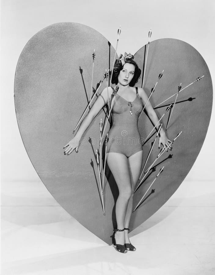 Женщина окруженная стрелками на огромном сердце (все показанные люди более длинные живущие и никакое имущество не существует Th г стоковое фото
