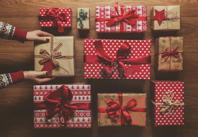 Женщина организуя красиво обернутые винтажные подарки на рождество, изображение с помохом, осматривает сверху стоковые изображения