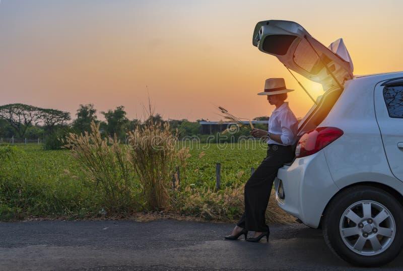 Женщина ослабляя внутри багажника автомобиля и наблюдая на красивой природе стоковое фото
