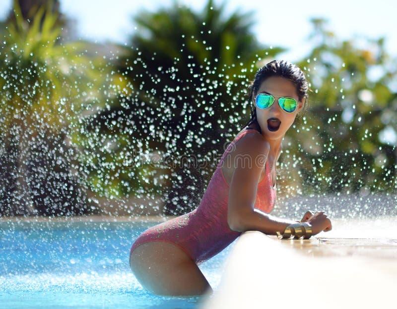 Женщина ослабляя в голубом роскошном отдыхе бассейна на белых естественных праздниках каникул камней стоковая фотография