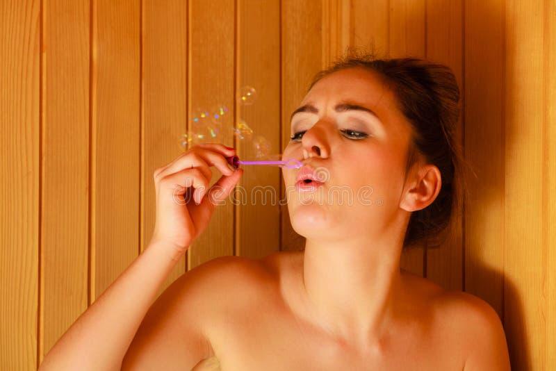 Женщина ослабляя в пузырях мыла комнаты сауны дуя стоковое изображение rf