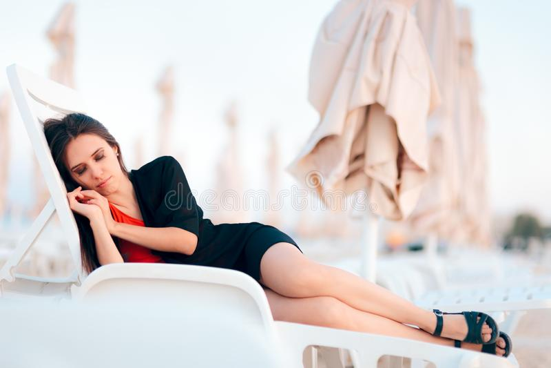 Женщина ослабляя на кресле для отдыха на пляже стоковое изображение rf