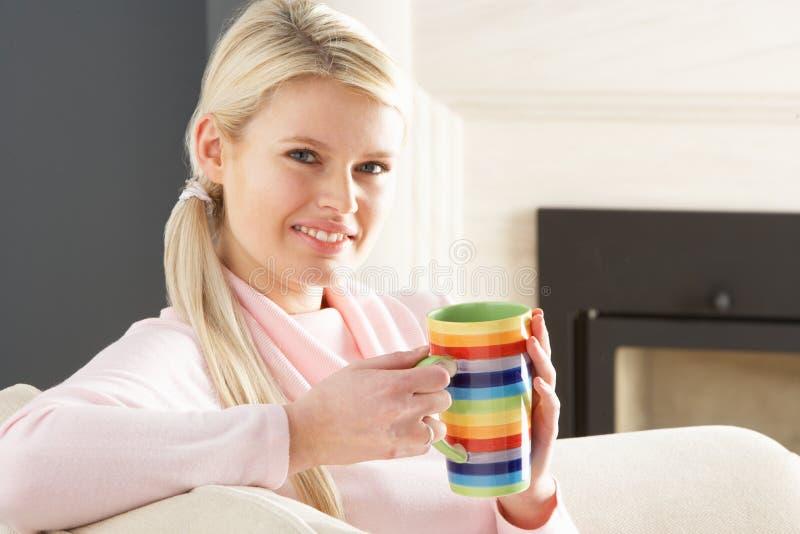 Женщина ослабляя на софе дома выпивая кофе стоковые изображения rf