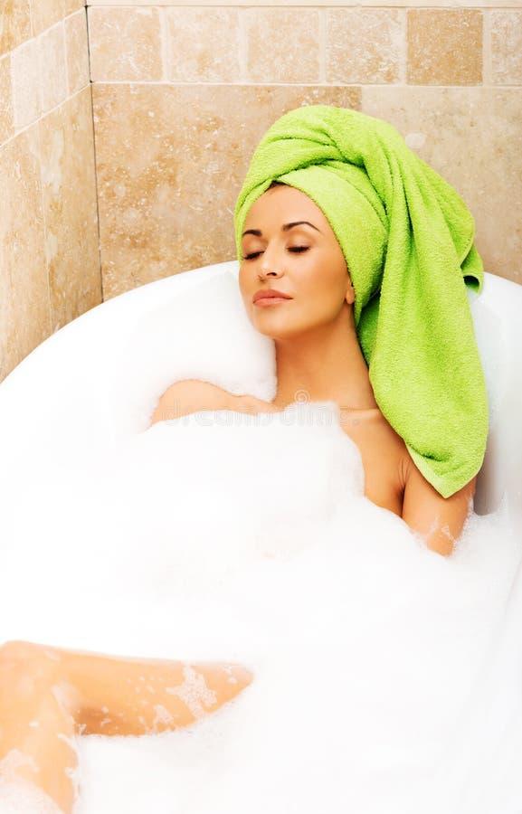 Женщина ослабляя в ванне при закрытые глаза стоковое фото rf