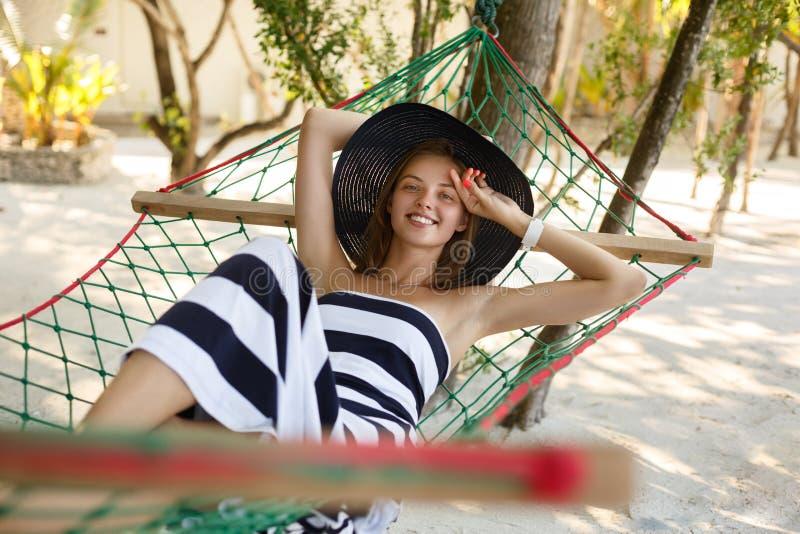 Женщина ослабляя в гамаке на тропическом пляже в тени, горячем солнечном дне Девушка смотрит к камере с улыбкой стоковые изображения rf