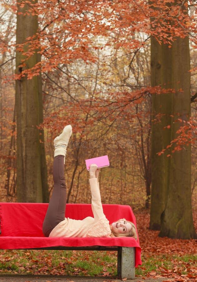 Женщина ослабляя в книге чтения парка падения осени стоковое фото rf